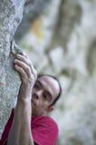 Climber grip. A rock climber ascending cliff face on an overhang Stock Photography