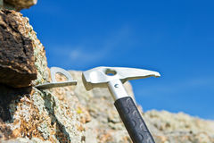 The climber hammers in hook for carbine into rock Royalty Free Stock Images