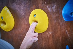 Climber hand on the bouldering climbing wall round grip. Close-up Stock Photos