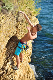 Climber hanging by a cliff Stock Images
