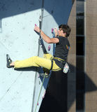Climber hanging on climbing Wall at Competitions Royalty Free Stock Images