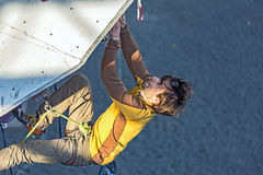 Climber hanging on climbing Wall at Competitions Stock Photo