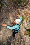 Climber in helmet overcomes rocky wall with rope insurance. Climber in helmet overcomes rocky wall with a rope insurance royalty free stock photo