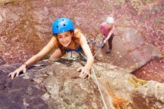Climber in helmet reaching top of the mountains stock image