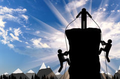 Climber helps ascent of two climbers on a mountain top Royalty Free Stock Photo