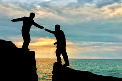 Climber helps friend in mountains of giving helping hand over precipice Stock Image