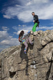 Climber helps her partner to rich the summit Royalty Free Stock Photography