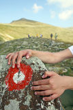 Climber is holding rock. Climber`s hands on the rock with mountains sign Stock Photography