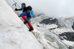 Climber with ice axes. On snow alpinist route, rocky mountain peaks and glacier. Alpinist with equipment - ice axe, crampons and rope. Beautiful scenery Stock Photos
