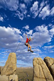 Climber jumping across gap. Royalty Free Stock Image