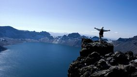 Climber and lake. An chinese man in peak of changbai mountain Royalty Free Stock Image