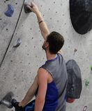 Climber looking for hold 2 limbs. Rock Climber with two limbs holding on to wall royalty free stock photo