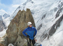Climber looking on snow alpinist route. Rocky mountain peaks and glacier. Alpinist with equipment - ice axe, crampons and rope. Beautiful scenery, mountain royalty free stock photo