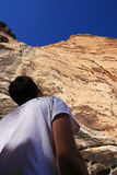 Climber looks up at cliff royalty free stock photography