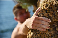 Climber making efforts to succeed. Gocus on the hand Royalty Free Stock Photography