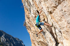 Climber making risky Move on dangerous Rock. Rock Climber hanging on dangerous Wall avoiding Failure and Fall down Stock Photos