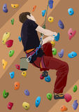 Climber man. Man climbing a climbing wall panel covered with colored holds for rock climbing training Stock Photo