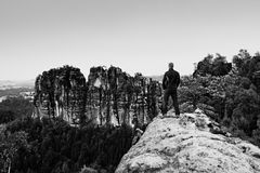 Climber man in black on sharp cliff and watch to mountains. Dark silhouette of rocks. Stock Photos