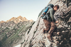 Climber Man climbing rocky mountains. With backpack Travel Lifestyle concept adventure summer vacations outdoor mountaineering sport risk and endurance Royalty Free Stock Image