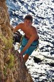 Climber Man climbs on rocky wall Stock Image