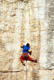 Climber.A man climbs on a wall against the sea. Royalty Free Stock Photo