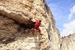 Climber.A man climbs on a wall against the sea. Royalty Free Stock Photos