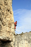 Climber.A man climbs on a wall against the sea. Royalty Free Stock Photography