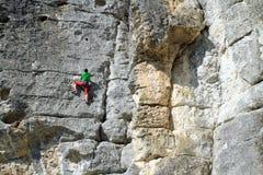 Climber.A man climbs on a wall against the sea. Stock Photography