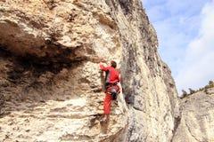 Climber.A man climbs on a wall against the sea. Stock Photo