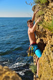 Climber man hanging by a cliff Stock Image