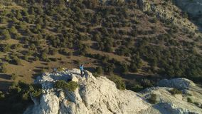 Climber man is standing on top of rock and raising hands victoriously. Aerial View. Drone is orbiting around stock footage