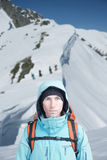 Climber man stands in winter mountains, Snowboarders walking uphill for freeride in the background. Stock Photo
