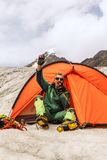 The climber in mountain camp in tent. The person in tent causes the help with handheld transceiver in mountains Stock Photo