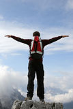 Climber on a mountain top stretching his arms like flying Royalty Free Stock Photo