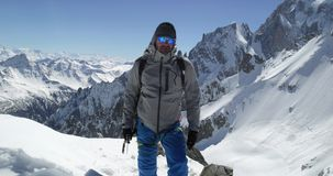 Climber mountaineer man portrait on snowy mount top in sunny day.Mountaineering ski activity. Skier people winter snow stock video footage