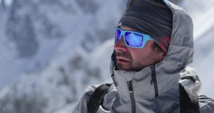 Climber mountaineer man portrait on snowy mount top in sunny day.Mountaineering ski activity. Skier people winter snow