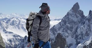 Climber mountaineer man reaching snowy mount top with ice axe in sunny day.Mountaineering ski activity. Skier people stock footage