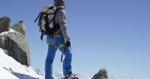 Climber mountaineer man reaching snowy mount top with ice axe in sunny day. Mountaineering ski activity. Skier people