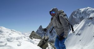 Climber mountaineer man reaching snowy mount top with ice axe in sunny day.Mountaineering ski activity. Skier people stock video footage