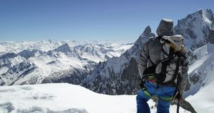 Climber mountaineer man reaching snowy mount top success in sunny day.Mountaineering ski activity. Skier people winter stock footage