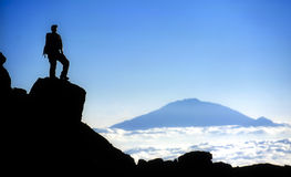 Climber on Mt Kilimanjaro with view of Mt Meru. Climber on the ascent of the upper slopes of Mt Kilimanjaro. Mt. Kilimanjaro and Uhuru Peak at 5895m is the Royalty Free Stock Image