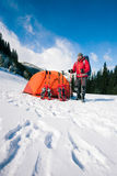Climber near the tent with snowshoes. Royalty Free Stock Images