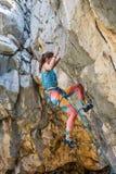 A girl climbs a rock royalty free stock photo