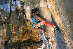 A girl climbs a rock royalty free stock photography