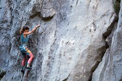 A girl climbs a rock royalty free stock images