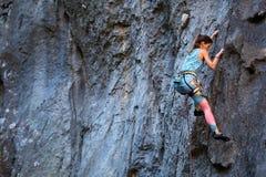 A girl climbs a rock stock photos