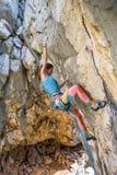 A girl climbs a rock stock photo