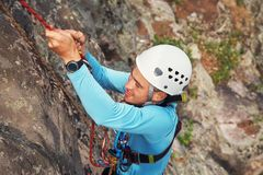 Climber overcomes rocky wall. Climber in helmet overcomes rocky wall with a rope insurance Royalty Free Stock Images