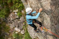 Climber overcomes rocky wall. Climber in helmet overcomes rocky wall with a rope insurance Stock Images