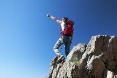 Climber pointing. To somewhere over deep blue sky; horizontal frame Stock Photo